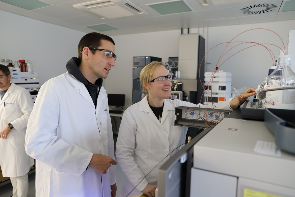 Two AbbVie Germany R&D scientists smiling at a machine