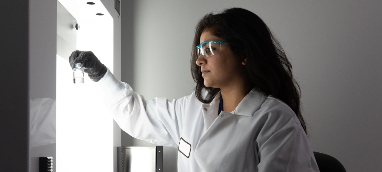 Female scientist holding clear liquid in a small jar.