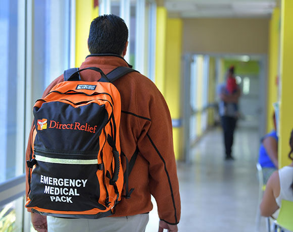 "A man walking through a hallway wearing a backpack that says ""direct relief, emergency medical pack"""