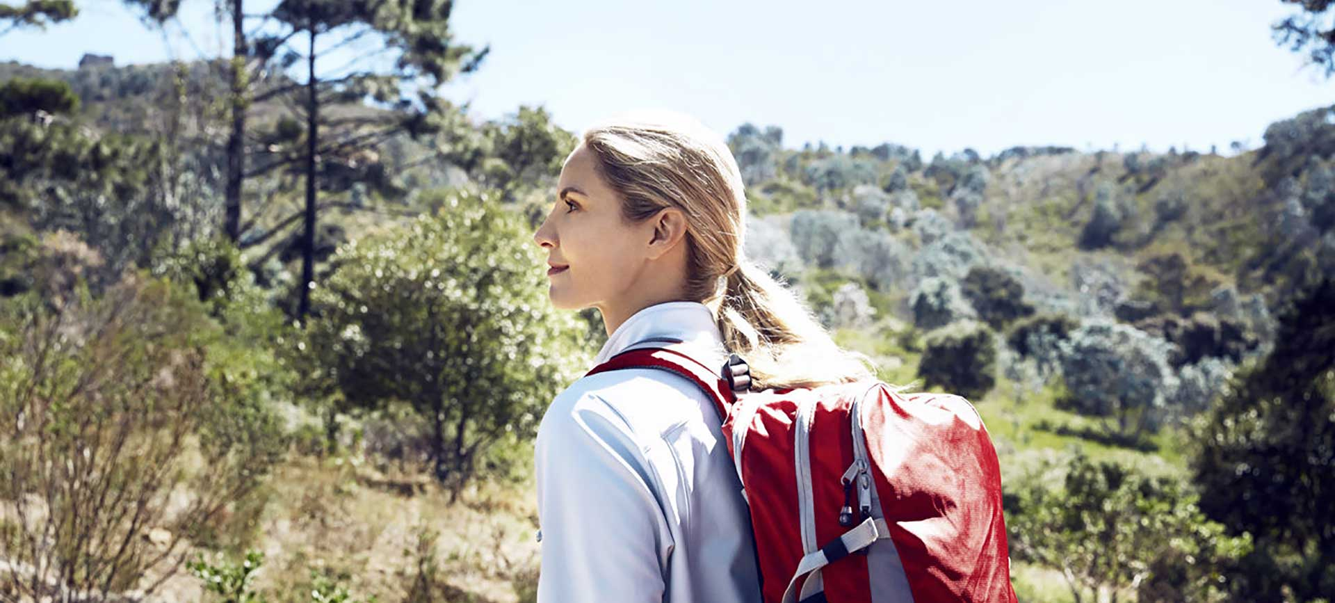 A young woman walking through trees with a red backpack