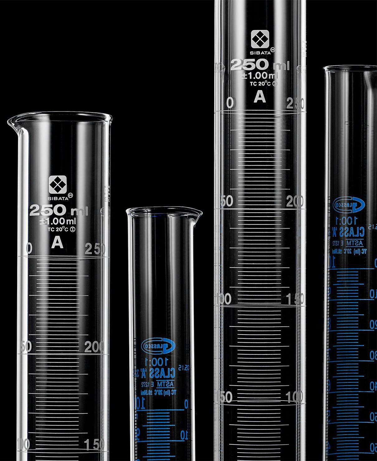 Four graduated cylinders of various sizes on a black background.