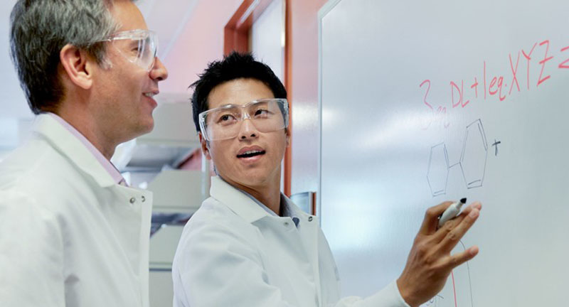 two men in lab coats and goggles. One facing the other and writing on a whiteboard.