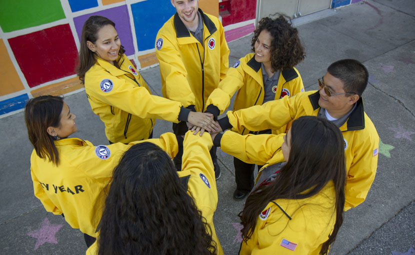 People in yellow jackets with their hands clasped in a circle