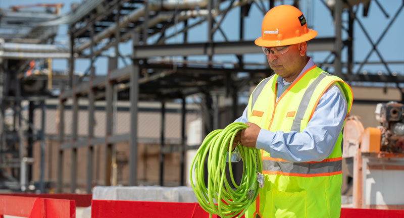 Construction worker winding a green tube.