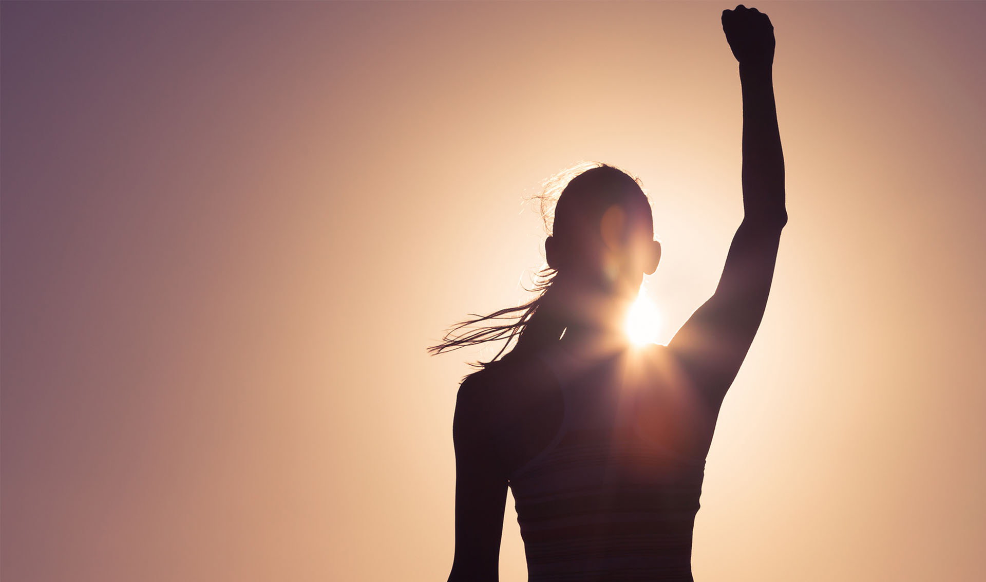 A sillouette of a woman in the sunset with her right fist in the air