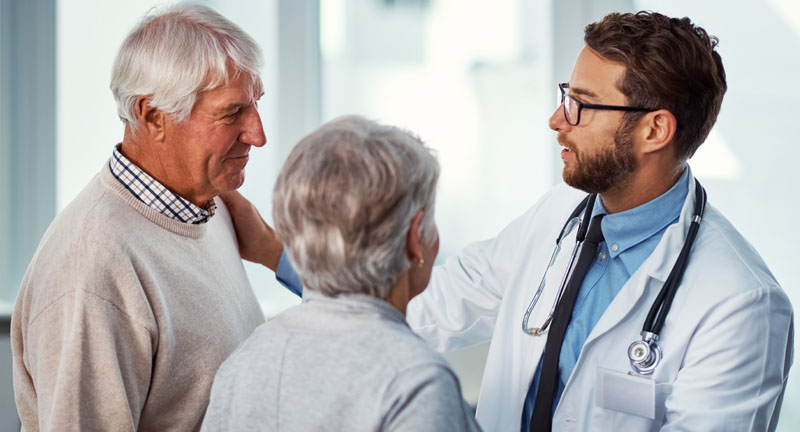 A young man with a stethoscope talking to an older man and woman