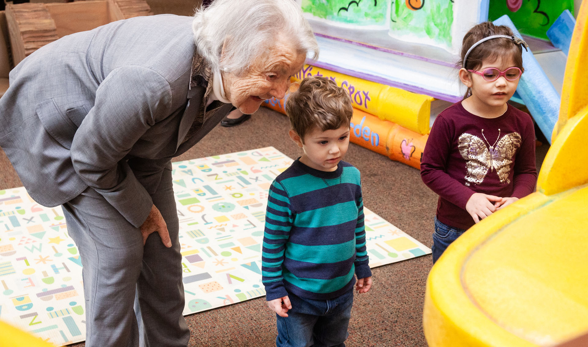 An elderly woman bent over smiling next to two small children in a daycare