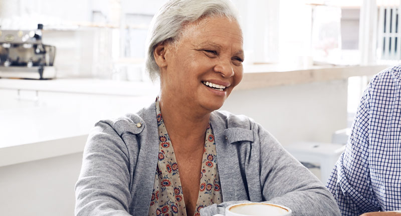 An older woman facing the camera and smiling into the distance