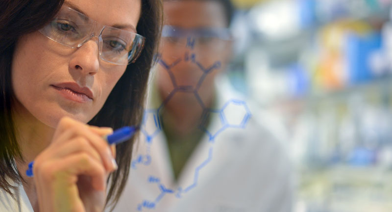 A female scientist drawing a diagram on a whiteboard in blue pen.