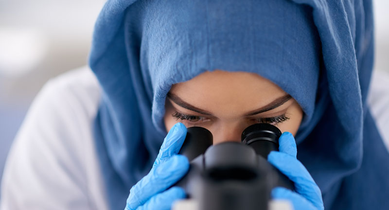 Female scientist looking into a microscope.