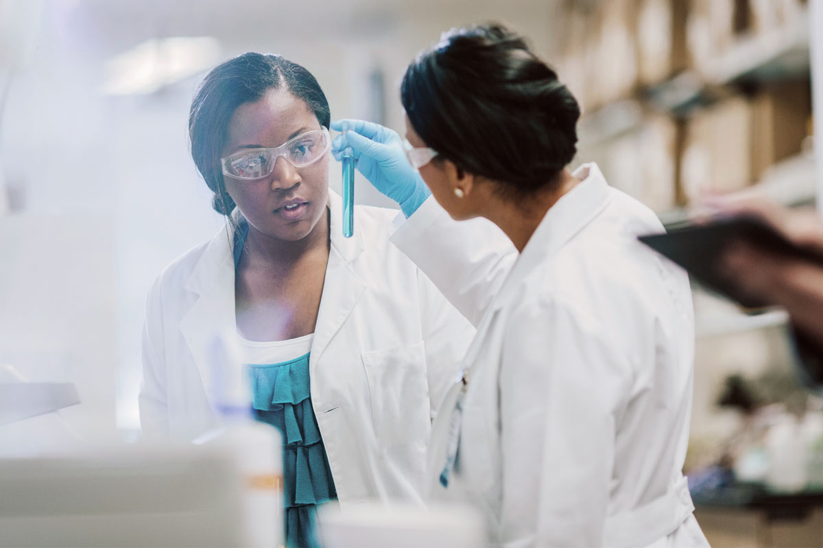 Two women in lab coats looking at a test tube filled with blue liquid