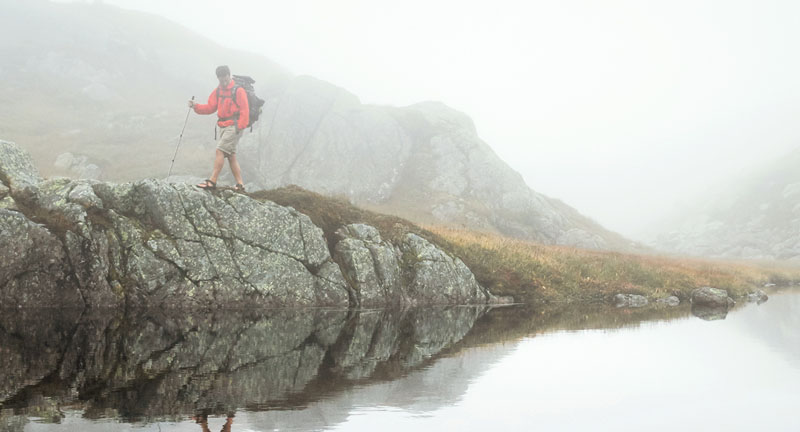 Male hiker walking on a rock near the water.