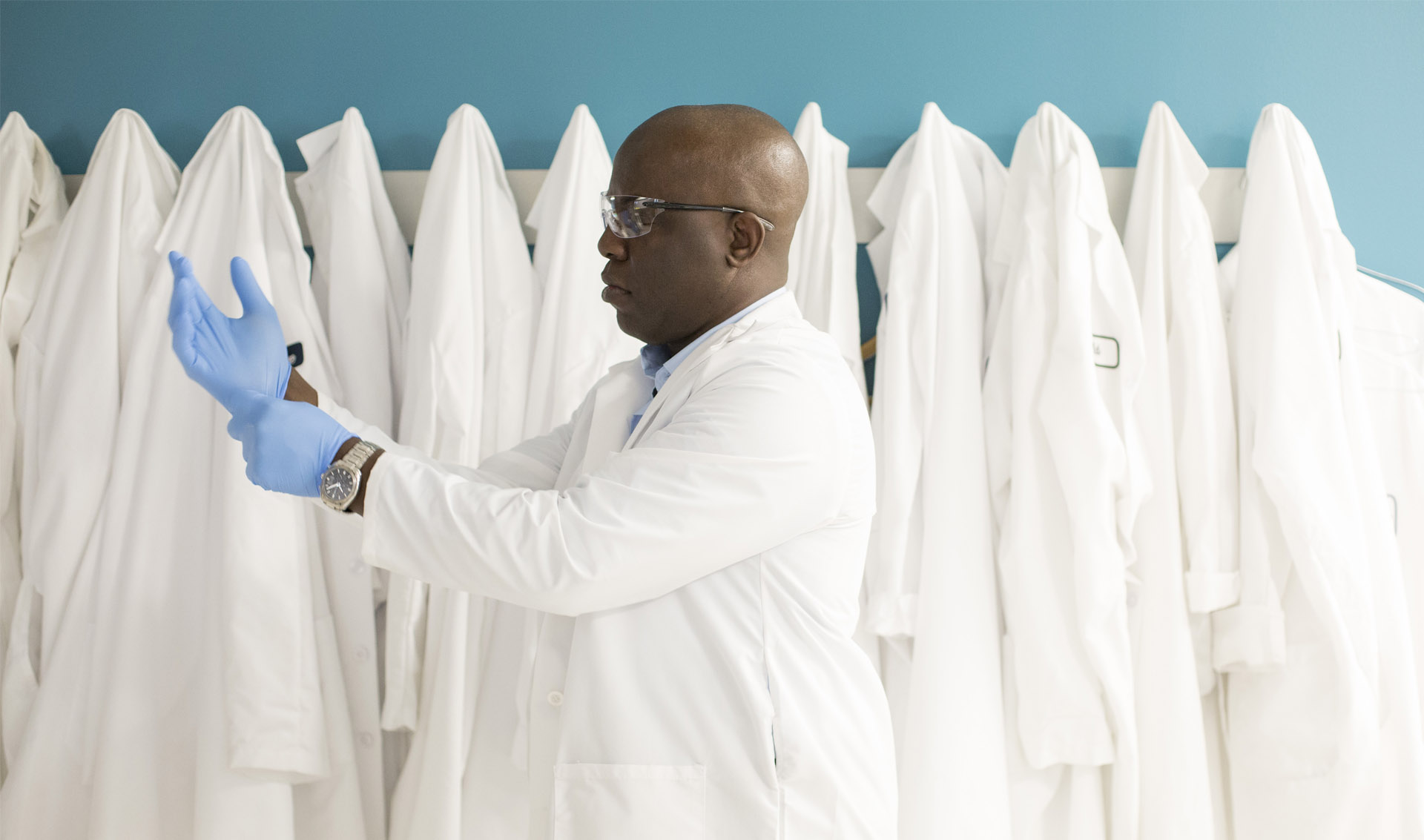 A scientist in a lab coat putting on blue gloves.