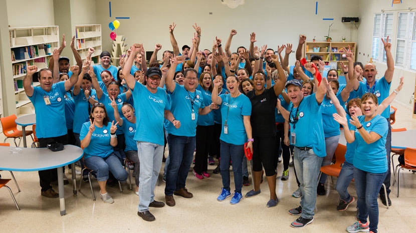 A group of individuals in matching blue abbvie shirts, smiling