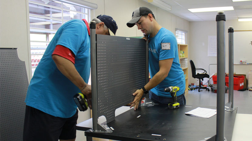 Two AbbVie team members assembling furniture in Puerto Rico.