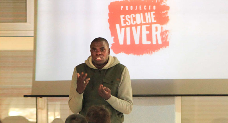 Black man speaking to ground in front of an Escolhe Viver sign