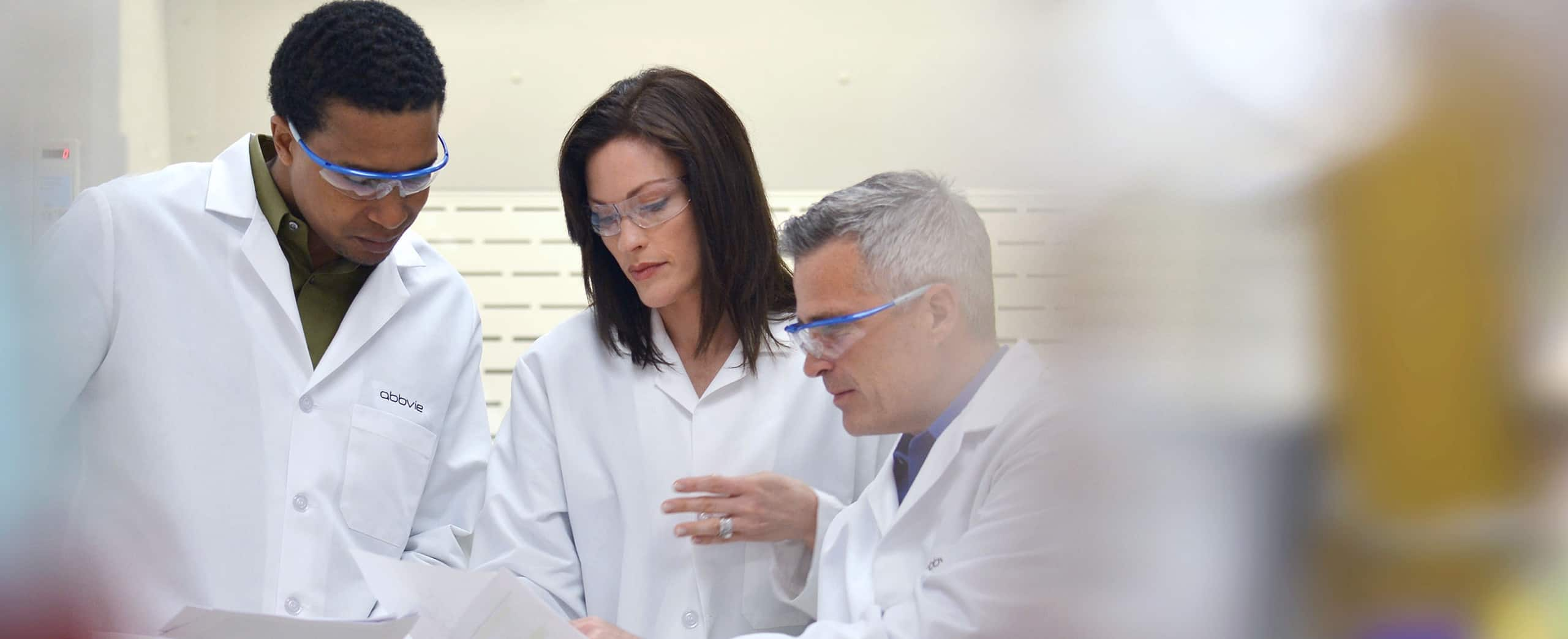 A woman and two men in abbvie labcoats reading off a sheet of paper