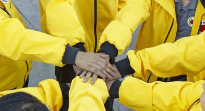 Close up of hands joined in the center of people wearing yellow jackets