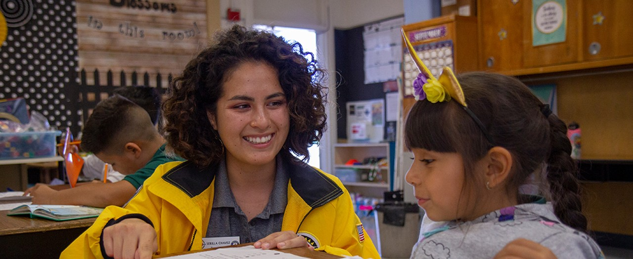 Woman in yellow jacket smiling while teaching a child in a classroom